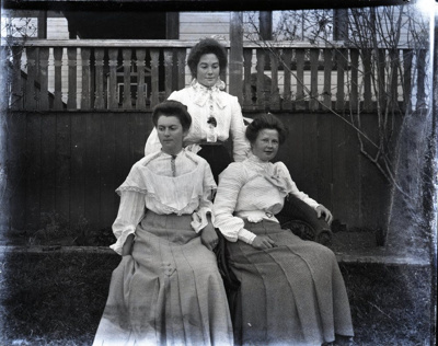 Photograph -  Three women posing outside in front of house with porch balusters in background. ; Aitken, John; 2017.1.297