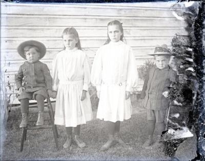 Aitken kids: Ellen, Dorothy, Roy and John, posed in front of a house; Aitken, John; 2017.1.078