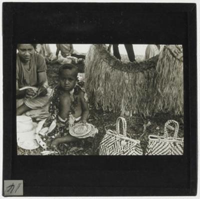 Lantern Slide - Child Sitting Amongst Handcrafts, Pacific Islands, circa 1930s; MV.MM.113739