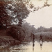Postcard showing three boys crossing the River Roding via stepping stones; ARN0198