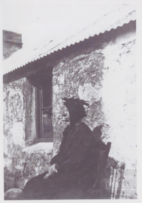 Old lady in long black dress and black mutch sitting on chair outside house; ULMPH 2000 0577