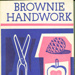 """Front cover of """"Brownie Handwork"""" book, featuring a pair of scissors and craft materials"""