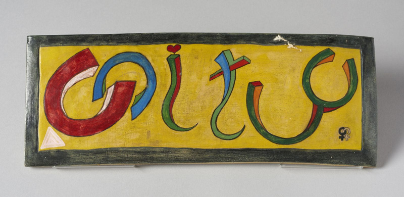 Rectangular plaque made by Gheni York bearing the word Unity in bright colours