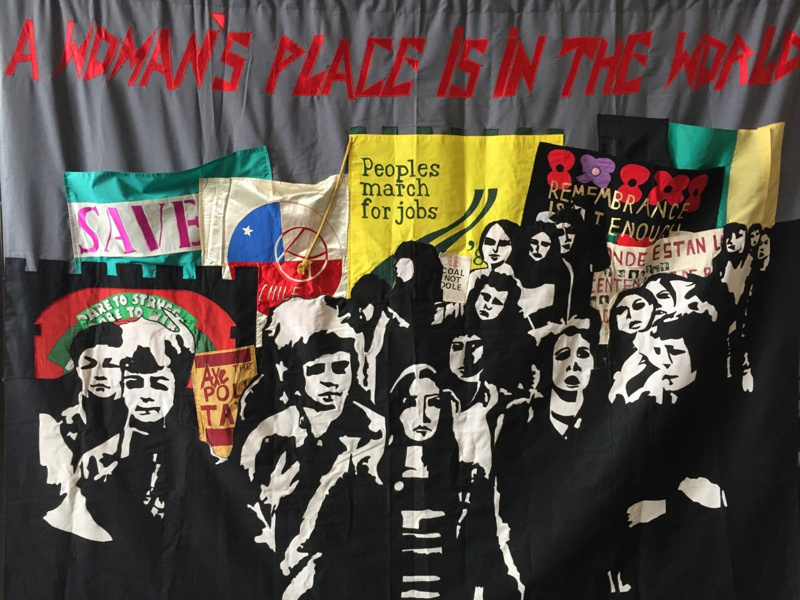 Banner titled 'A Woman's Place Is In The World' (1987) by Clare Higney