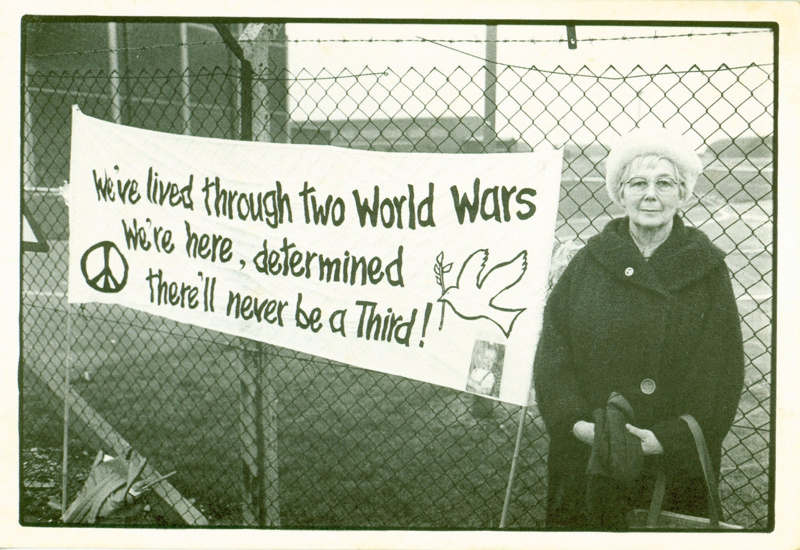 The Common Cause (8) postcard featuring a photograph of a woman standing beside an anti-war bannerers Ltd; Leeds Postcards; 1983; 2014.49.3
