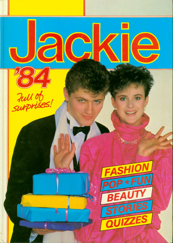 "Front cover of Jackie Annual '84, featuring a heterosexual couple beside the tagline ""Full of surprises!"" and promising Fashion, Pop, Fun, Beauty, Stories and Quizzes inside."