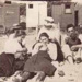 Group in day-clothes on beach; betw. 1914 and 1918; P2489